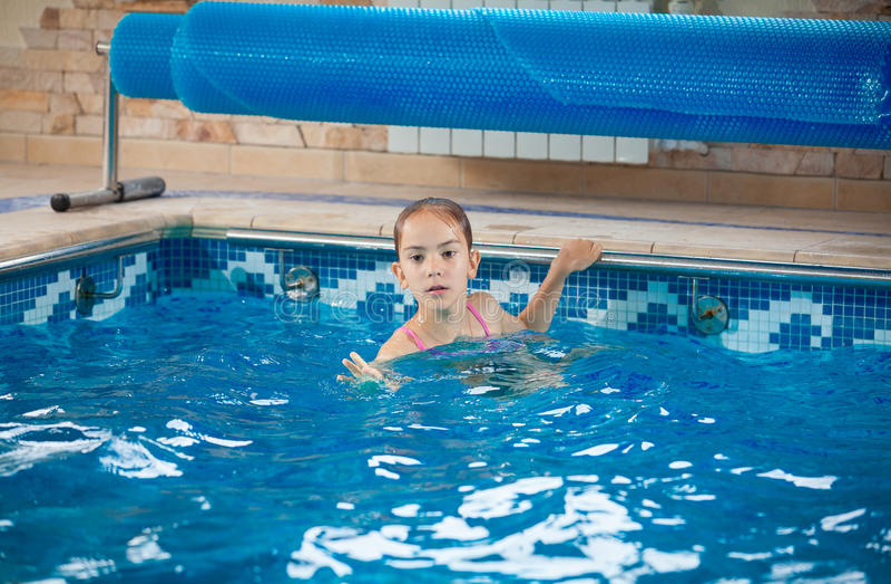 Jeune fille apprenant comment nager dans la piscine photos libres de droits