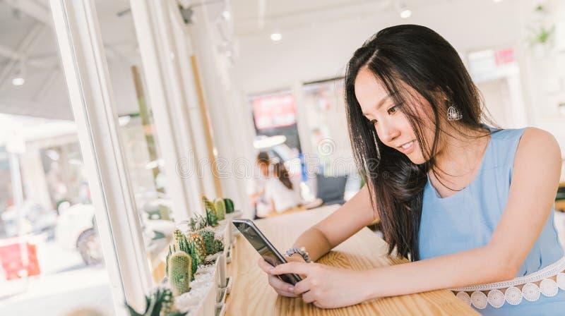 Jeune fille asiatique à l'aide du smartphone en café moderne de café ou de boulangerie Concept de technologie d'application de té images stock