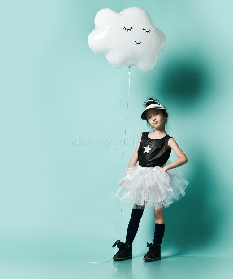 Jeune fille asiatique dans le ballon m?tallique de nuage de prise de jupe de mode pour l'anniversaire d'enfants sur la menthe ble image stock