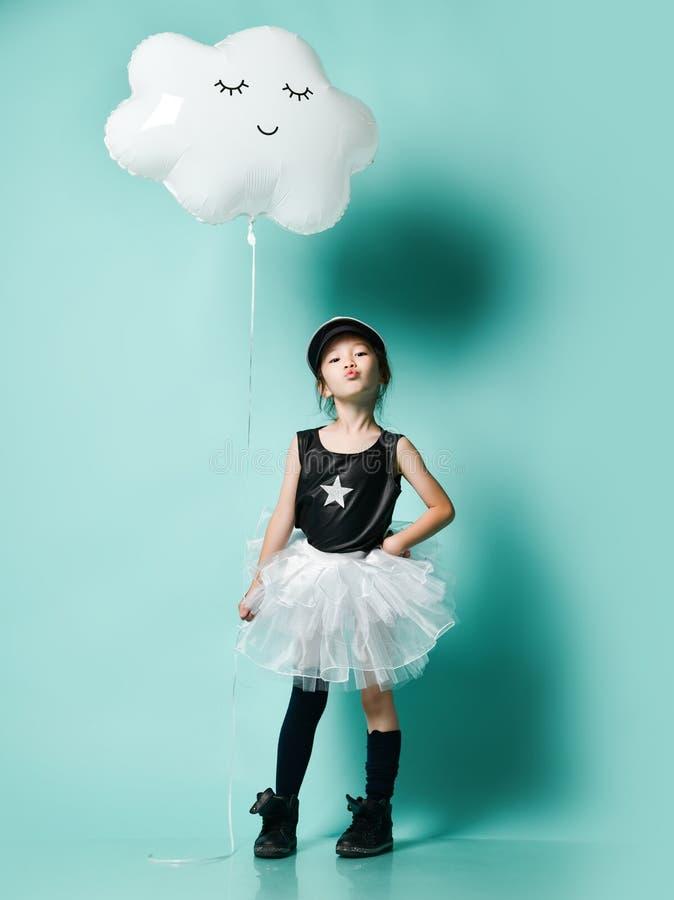 Jeune fille asiatique dans le ballon m?tallique de nuage de prise de jupe de mode pour l'anniversaire d'enfants sur la menthe ble photos libres de droits