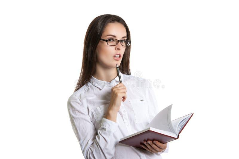 Jeune fille attirante avec des verres tenant le journal intime dans des mains images libres de droits