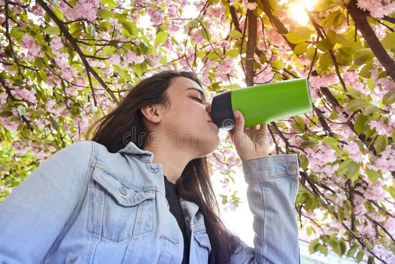 Jeune fille attirante buvant sur la rue de cerisier photos stock