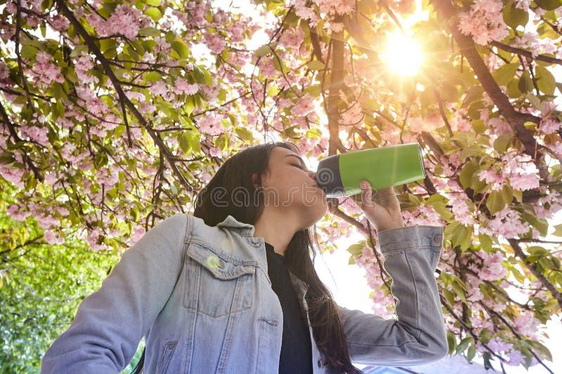Jeune fille attirante buvant sur la rue de cerisier image libre de droits
