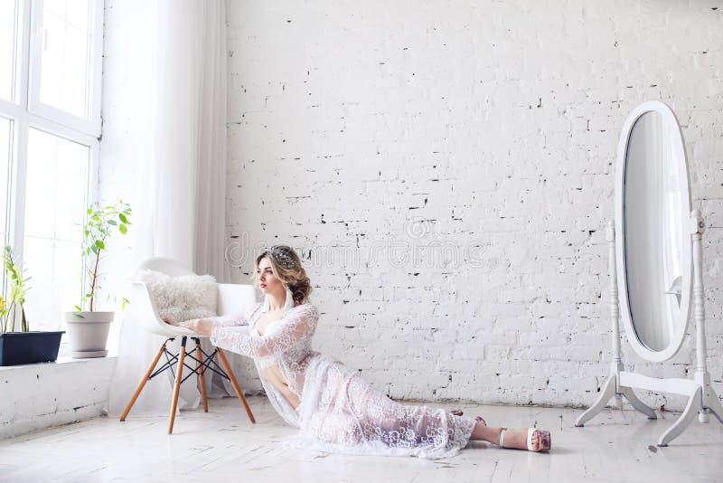 Jeune fille attirante dans les sous-vêtements et le déshabillé dans la chambre blanche près de la fenêtre Matin de jeune mariée image stock