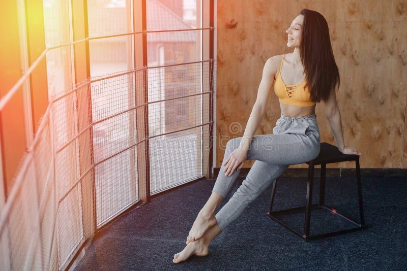 Jeune fille attirante de forme physique s'asseyant sur la chaise pr?s de la fen?tre sur le fond d'un mur en bois, se reposant sur photos libres de droits