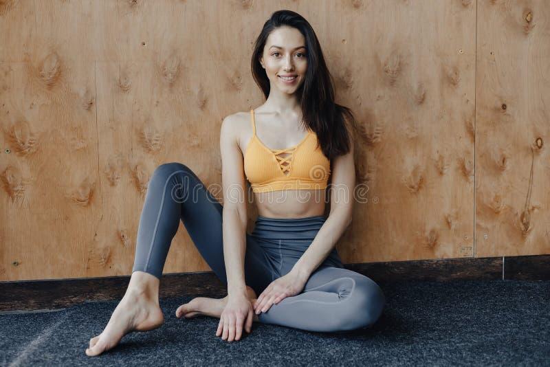Jeune fille attirante de forme physique s'asseyant sur le plancher pr?s de la fen?tre sur le fond d'un mur en bois, se reposant s images libres de droits