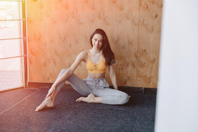 Jeune fille attirante de forme physique s'asseyant sur le plancher pr?s de la fen?tre sur le fond d'un mur en bois, se reposant s image libre de droits