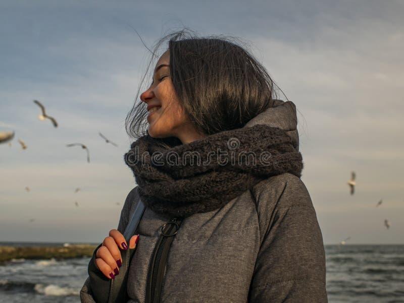 Jeune fille attirante de portraits sur le fond de la mer, du ciel et des mouettes photo libre de droits