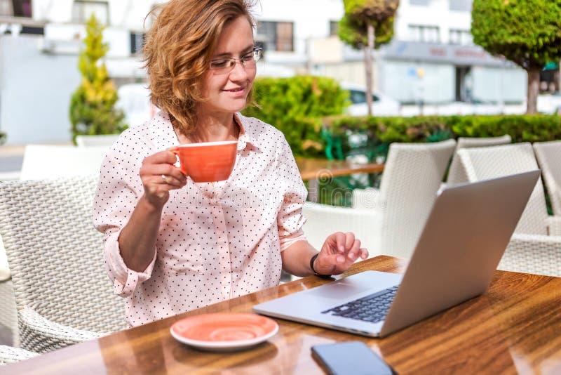 Jeune fille attirante en verres avec un ordinateur portable et une tasse de coff photos stock