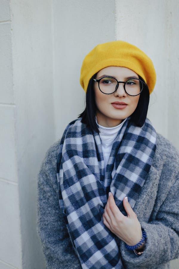 Jeune fille attirante en verres dans le manteau et le b?ret jaune sur un fond clair simple images libres de droits
