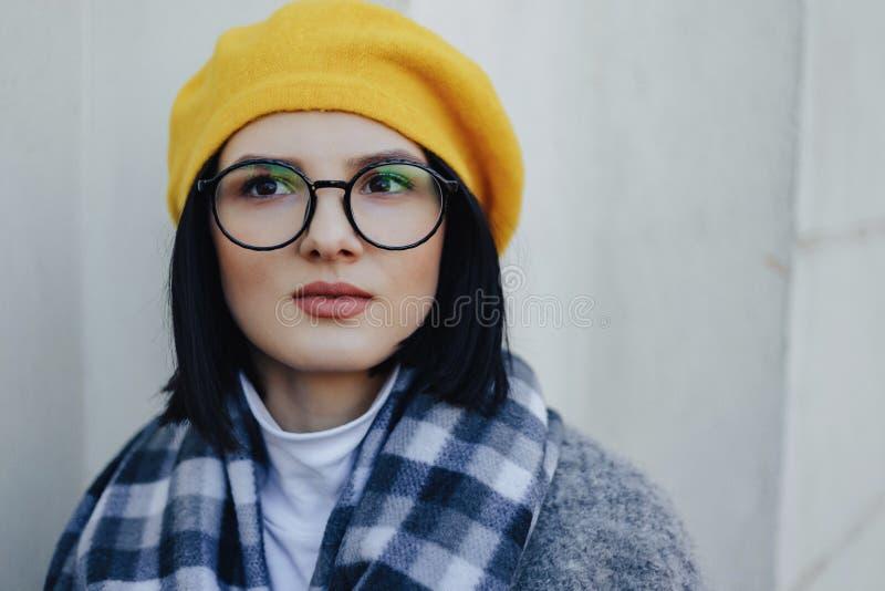 Jeune fille attirante en verres dans le manteau et le b?ret jaune sur un fond clair simple photos stock