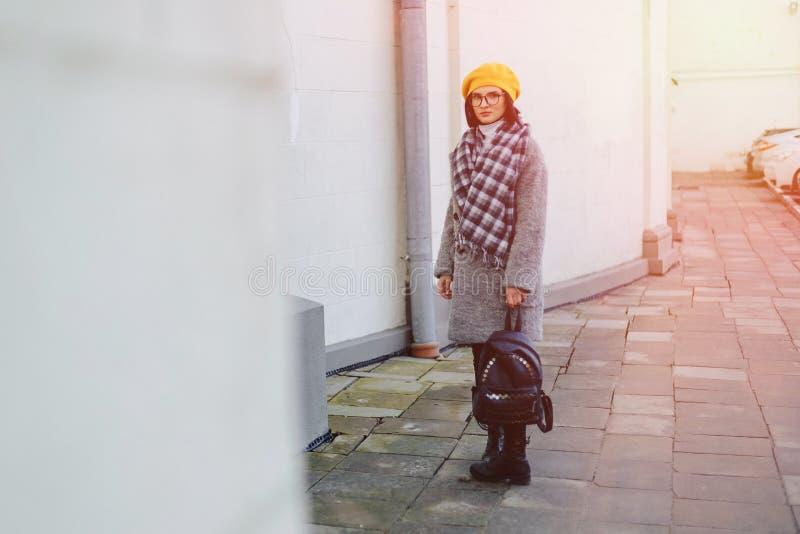 Jeune fille attirante en verres dans le manteau et la marche jaune de style libre de b?ret photographie stock