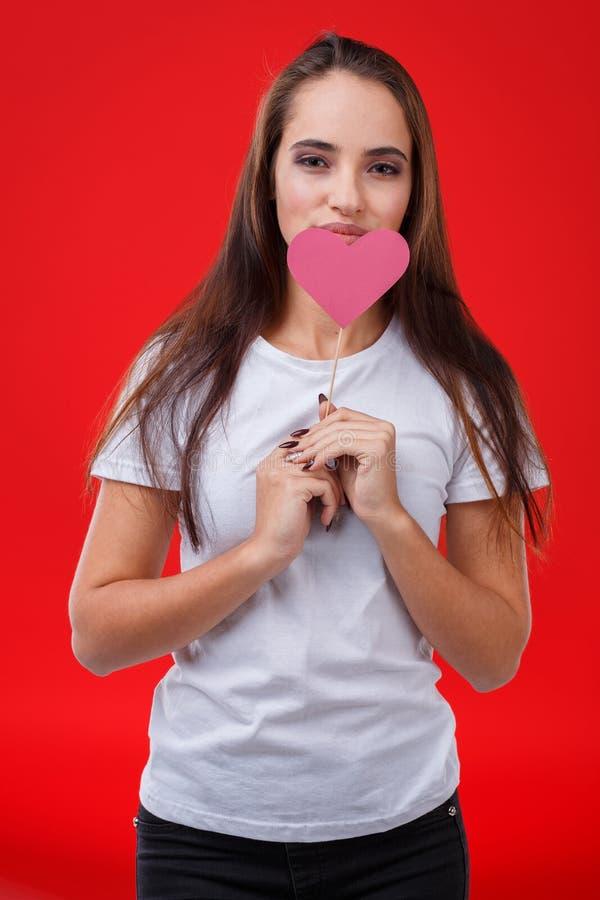 Jeune fille attirante, prises un coeur de papier rose sur un bâton près de son visage Sur un fond rouge photographie stock