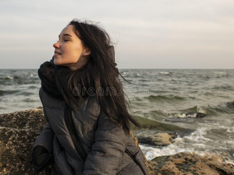 Jeune fille attirante s'asseyant sur une pierre près de la mer sur un fond de ciel gris photographie stock