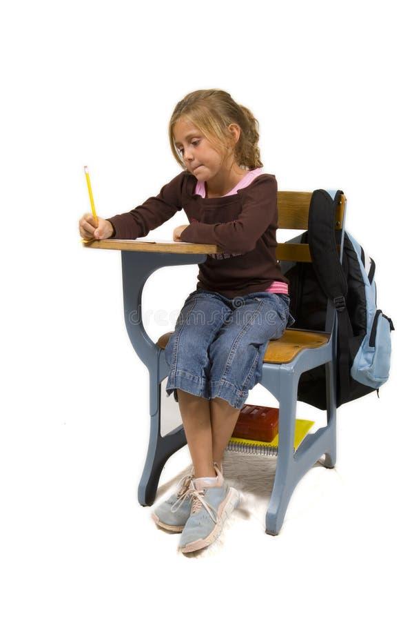 Jeune fille au bureau à l'école sur le blanc images libres de droits