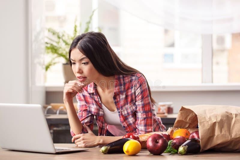 Jeune fille au mode de vie sain de cuisine se penchant sur des nouvelles de lecture de table sur l'ordinateur portable concerné p photo stock
