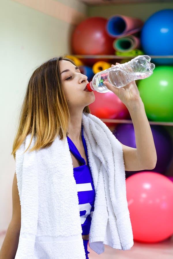 Jeune fille avec de l'eau potable de serviette d'une bouteille tandis que train photo libre de droits
