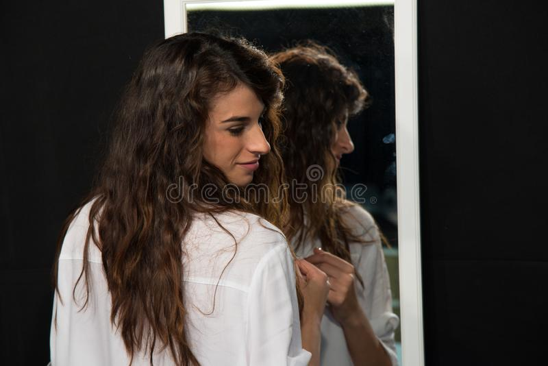 Jeune fille avec de longs cheveux bruns onduleux, une chemise d'hommes blancs de port photo libre de droits