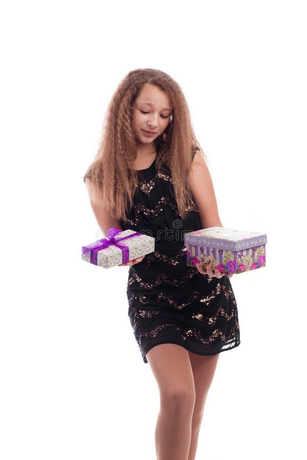 Jeune fille avec de longs cheveux dans la robe noire avec des cadeaux dans des mains sur un fond blanc photos stock