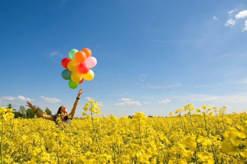 Jeune fille avec des ballons sur la zone de canola. image libre de droits