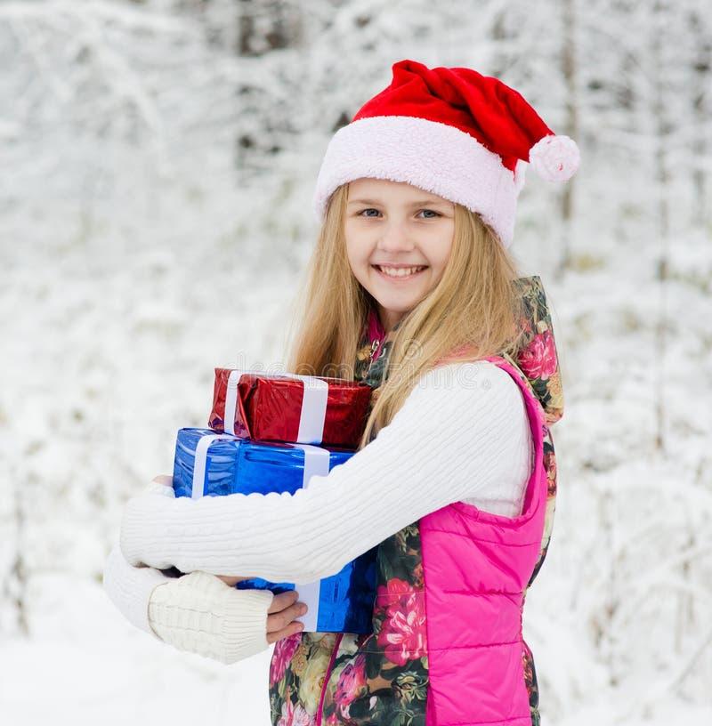 Jeune fille avec des boîte-cadeau de pile dans la forêt d'hiver photos stock
