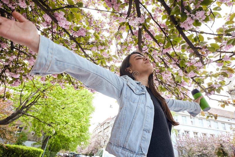 Jeune fille avec des bras grands ouverts tenant une tasse et enjoing la rue de cerisier image stock