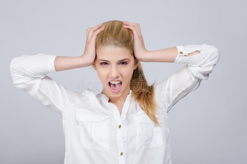 Jeune fille avec des mains sur sa tête étant cris désespérés. photographie stock libre de droits