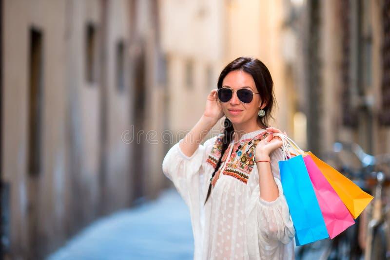 Jeune fille avec des paniers sur la rue étroite en Europe Portrait d'une belle femme heureuse tenant des paniers photo stock