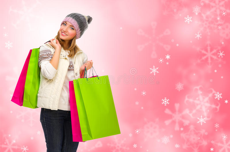 Jeune fille avec des sacs sur le fond d'hiver photographie stock libre de droits