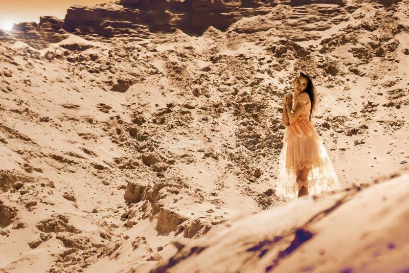 Jeune fille avec du charme dans la robe rose dans un désert images libres de droits