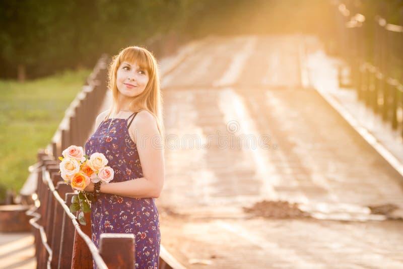 Jeune fille avec du charme se tenant sur un pont rustique au soleil d'aube avec un bouquet des roses photographie stock libre de droits