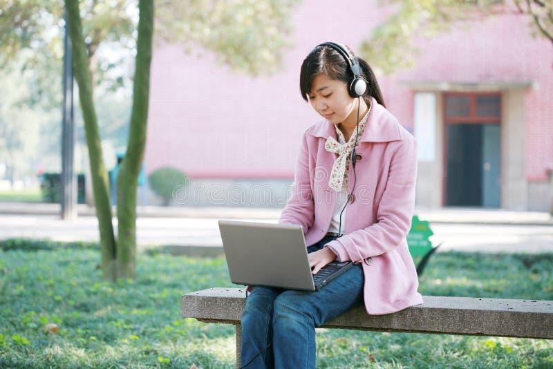 Jeune fille avec l'ordinateur portatif photographie stock