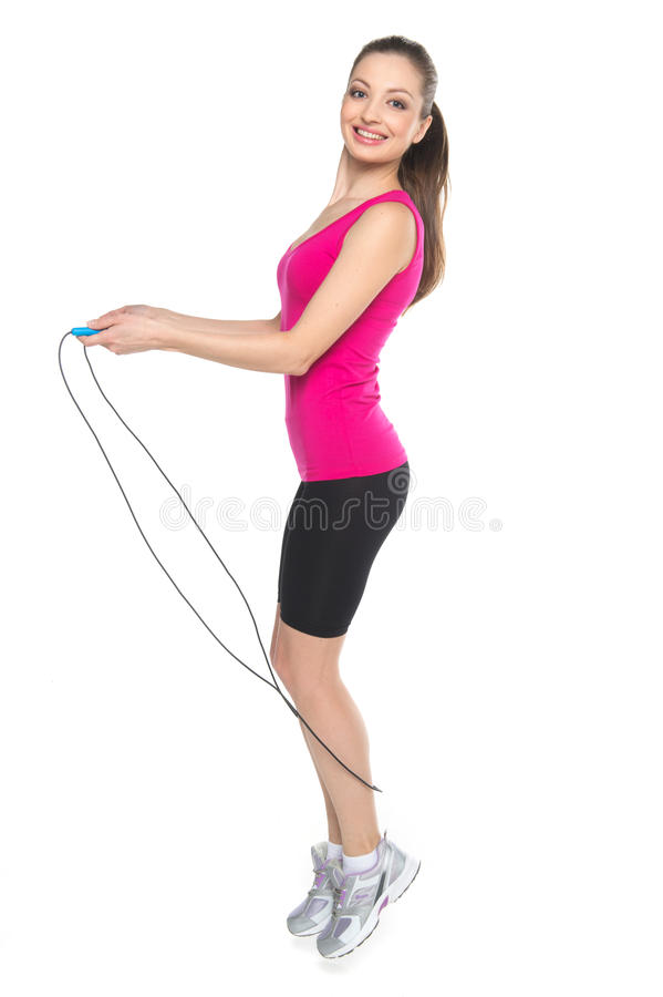 Jeune fille avec la corde à sauter sur le fond blanc photos stock