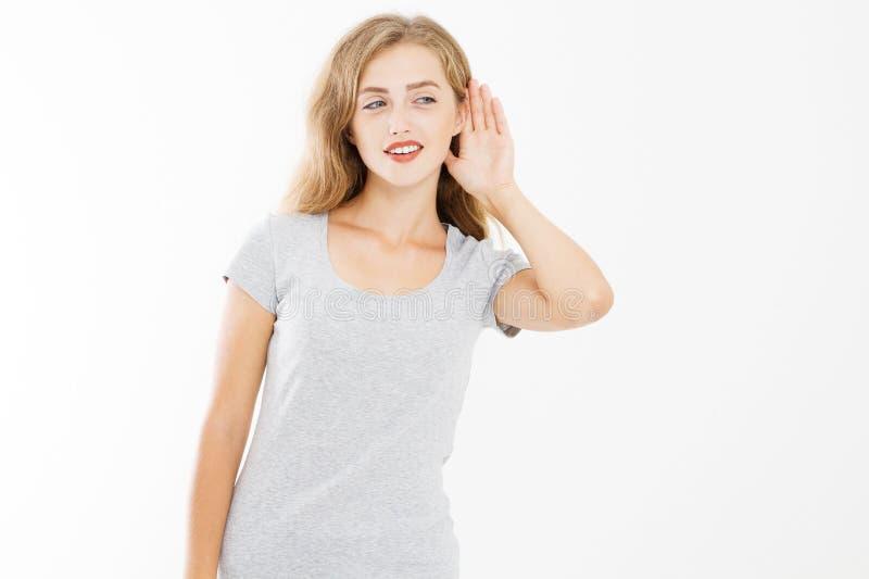 Jeune fille avec la femme d'intérêt écoutant et surprenant par son oreille d'isolement sur le blanc T-shirt d'été de calibre avec photos stock