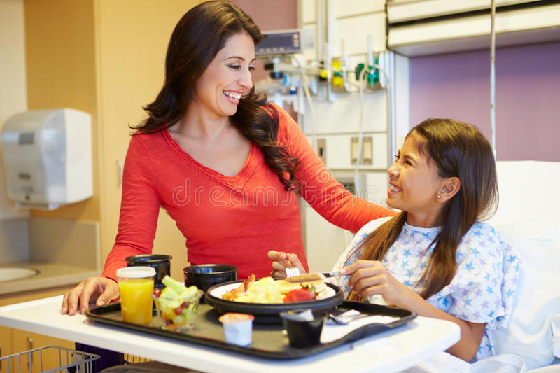 Jeune fille avec la mère mangeant le déjeuner dans le lit d'hôpital images stock