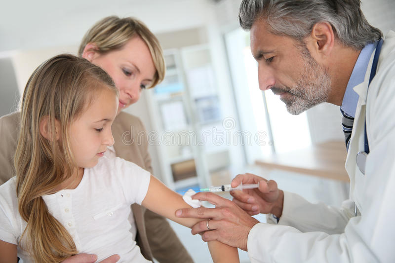 Jeune fille avec la mère obtenant vaccinée par le docteur photographie stock