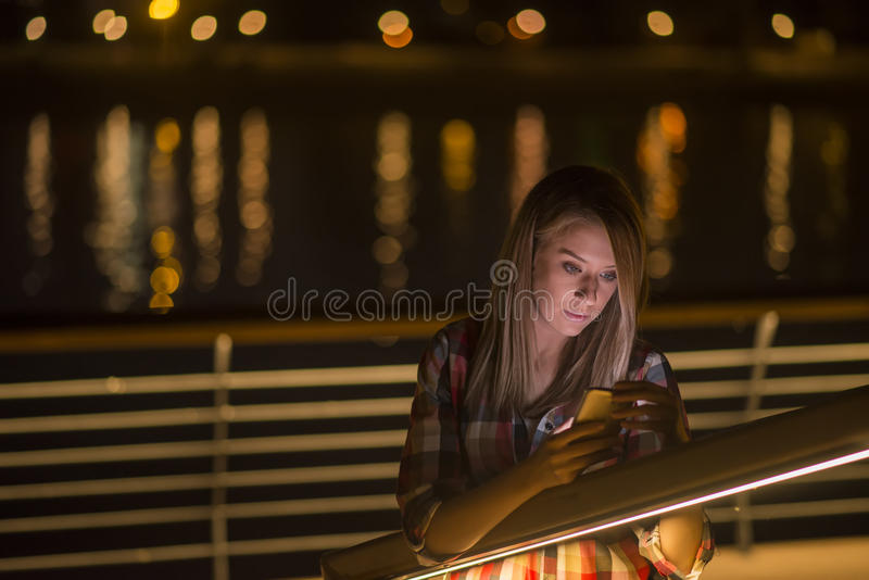 Jeune fille avec la mauvaise nouvelle whatching de Smart-téléphone dans l'Internet image stock