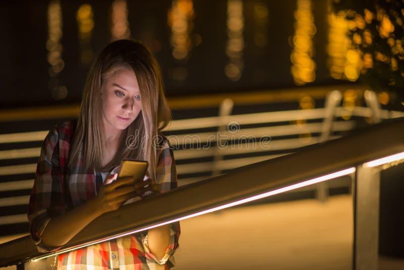 Jeune fille avec la mauvaise nouvelle whatching de Smart-téléphone dans l'Internet photo libre de droits