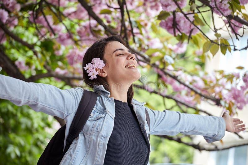 Jeune fille avec la position appréciante grande ouverte de soleil de bras sur le fond de Sakura de floraison photos stock