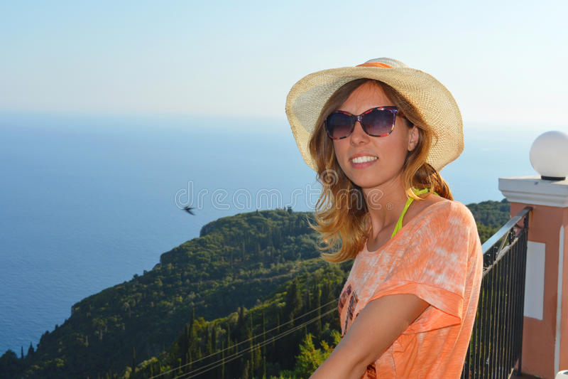 Jeune fille avec le chapeau de paille regardant le bord de la mer de l'extraordin photographie stock libre de droits