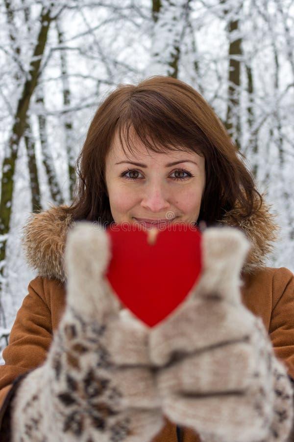 Jeune fille avec le coeur en bois rouge unfocused en quelques jour de valentines de forêt d'hiver et vacances de Noël Concept de  images stock