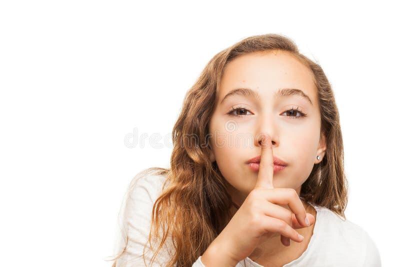 Jeune fille avec le doigt de participation sur ses lèvres sur le geste de silence d'isolement image libre de droits