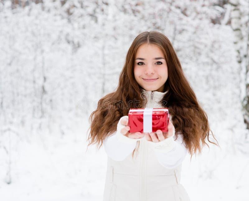 Jeune fille avec le petit boîte-cadeau rouge se tenant dans la forêt d'hiver photographie stock libre de droits
