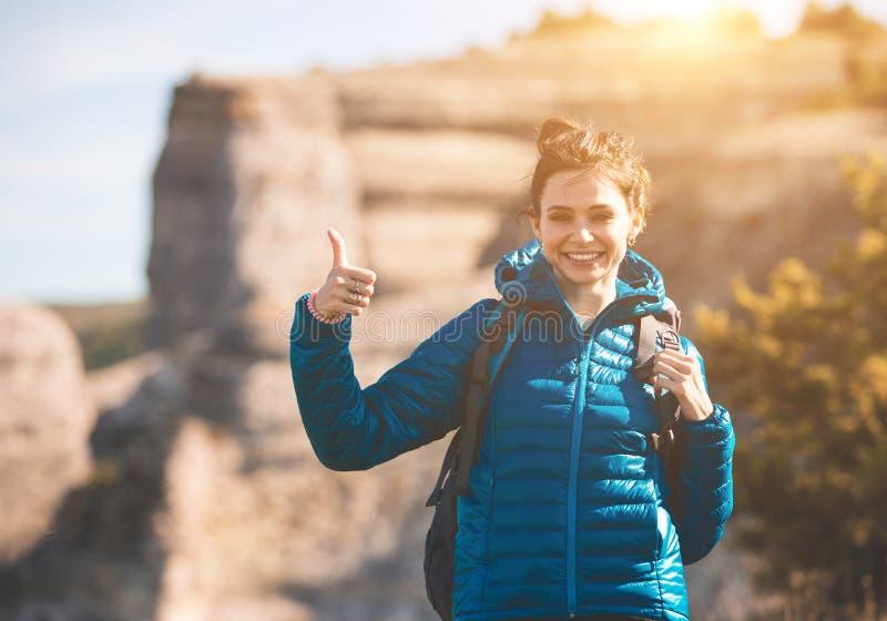 Jeune fille avec le sac à dos appréciant le coucher du soleil sur la montagne photos stock