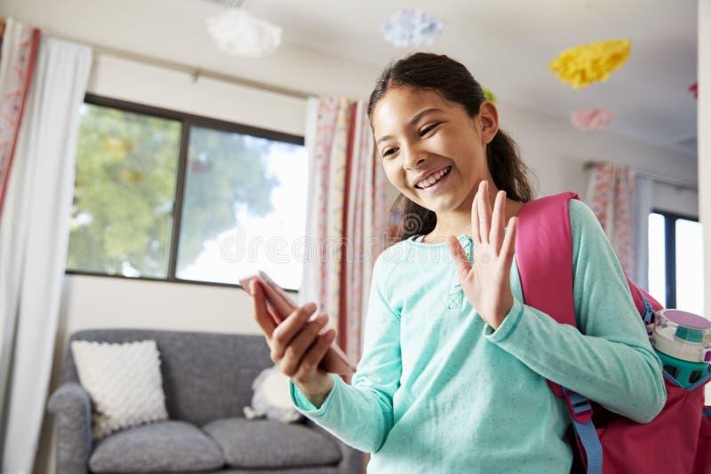 Jeune fille avec le sac à dos dans la chambre à coucher prête à aller à l'école faisant l'appel visuel au téléphone portable photographie stock libre de droits