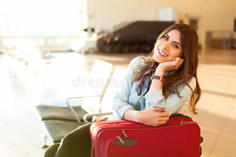 Jeune fille avec le sac de chariot dans l'aéroport photographie stock libre de droits