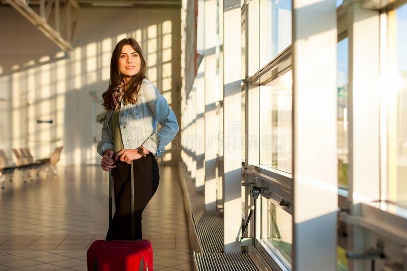 Jeune fille avec le sac de chariot dans la salle d'attente d'aéroport image stock