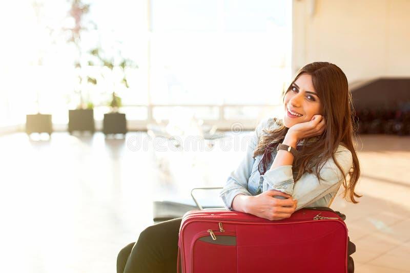 Jeune fille avec le sac de chariot dans la salle d'attente d'aéroport photos libres de droits
