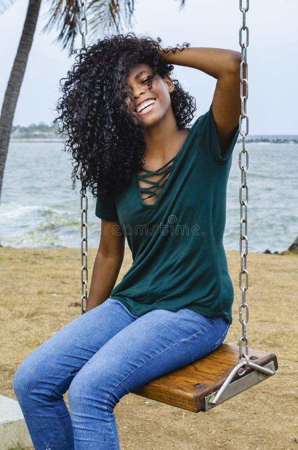 Jeune fille avec les cheveux noirs, cheveux riants se reposant sur une oscillation arrière à la mer des Caraïbes, appréciant un j photo stock