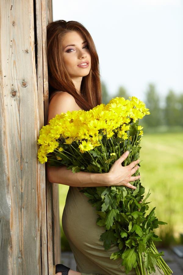 Jeune fille avec les fleurs jaunes photo stock